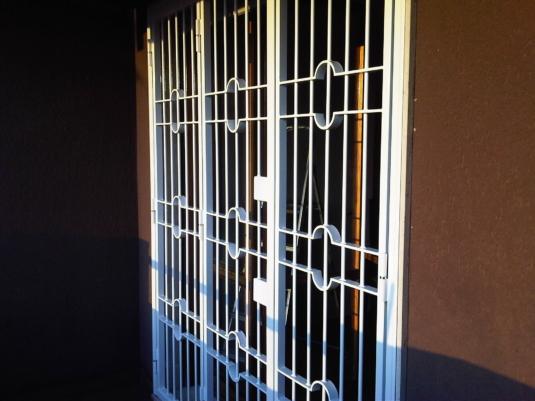 inferriate di sicurezza apribili parallele verticali con cerchi e semicerchi in ferro per porta finestra su balcone di villetta o condominio - Fratelli Gussoni fabbro Cornaredo