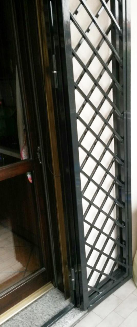 particolare di inferriate di sicurezza apribili incrociate a rombi in ferro per porta finestra di villetta o condominio - Fratelli Gussoni fabbro Cornaredo
